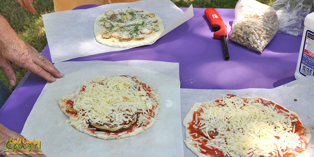 Three pizzas waiting to be baked