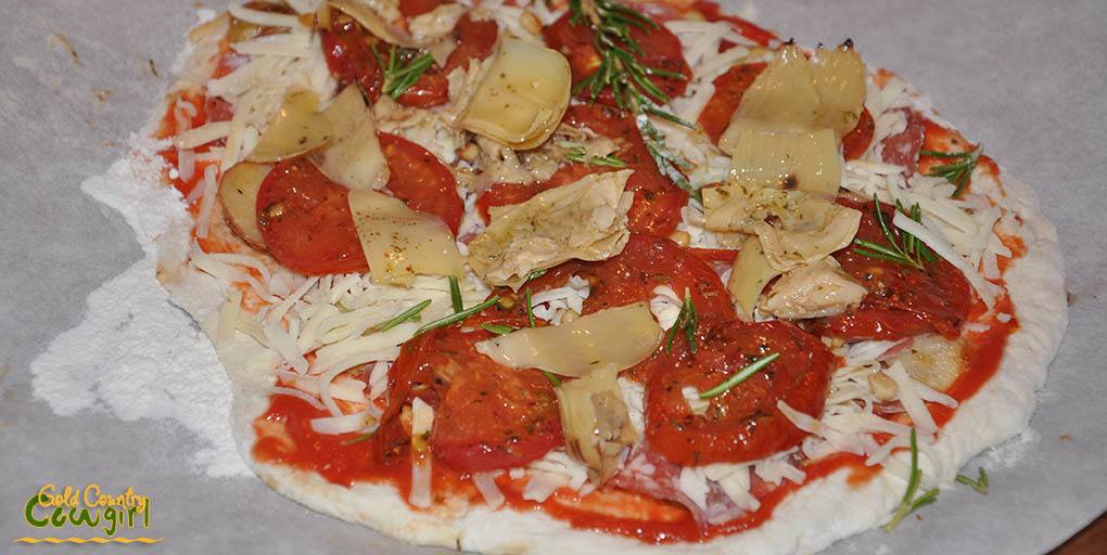 Pizza with artichokes, roasted tomatoes, fingerling potatoes ready for the outdoor pizza oven