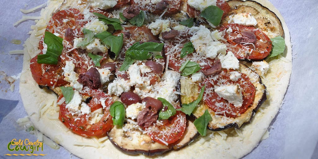 Pizza with basil olives feta ready for the outdoor pizza oven