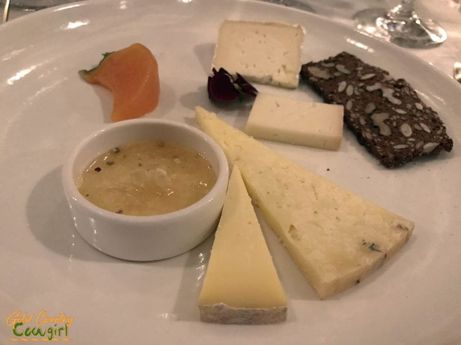 Cheese plate with accompaniments including bee pollen and wild honeycomb