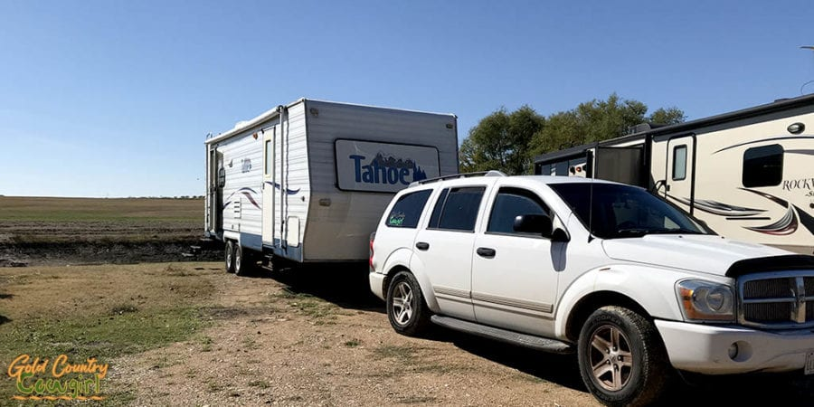 trailers and a tow vehicle by pond at Downtown Texas RV Park
