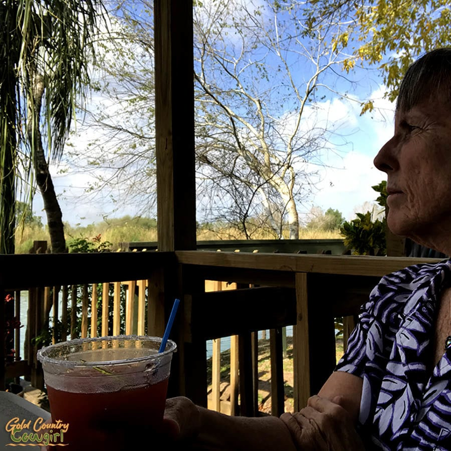 woman drinking a bloddy Mary on the patio overlooking the Rio Grande