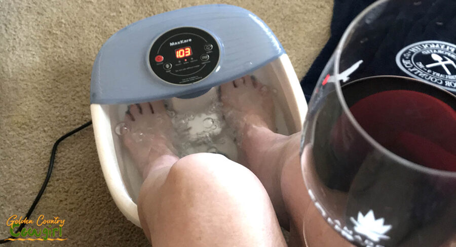 soaking feet in a foot bath holding a glass of wine
